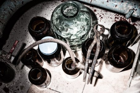 Top view of jars, sickle and tongs in stained laboratory